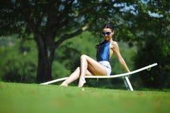 Mädchen, das in einem weißen Aufenthaltsraum auf grünem Gras sitzt stockfotos