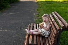 Mädchen, das einen Apfel auf der Bank isst Stockbilder