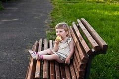 Mädchen, das einen Apfel auf der Bank isst Lizenzfreie Stockfotografie