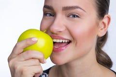 Mädchen, das einen Apfel beißt Lizenzfreie Stockbilder