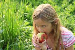 Mädchen, das einen Apfel isst Stockfotografie