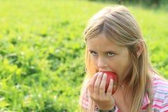 Mädchen, das einen Apfel isst Stockfoto
