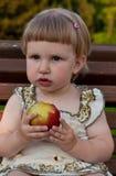 Mädchen, das einen Apfel isst Stockbild