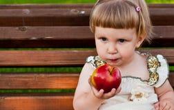 Mädchen, das einen Apfel isst Stockfotos