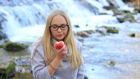 Mädchen, das einen Apfel nahe einem Wasserfall isst stock footage