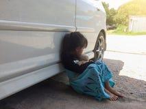 Mädchen, das einen Bären neben einem Auto umarmend sitzt lizenzfreies stockbild