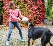 Mädchen, das einen Ball hält und mit schwarzem Hund spielt stockbild