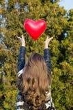 Mädchen, das einen Ballon in Form des Herzens wirft Lizenzfreies Stockfoto