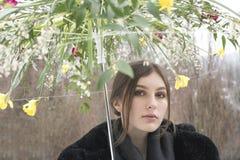 Mädchen, das einen Blumenregenschirm im Garten hält lizenzfreie stockbilder