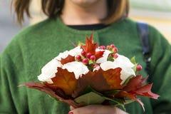 Mädchen, das einen Blumenstrauß von roten Beeren der weißen Rosen und von Ahorn leav hält Lizenzfreies Stockbild