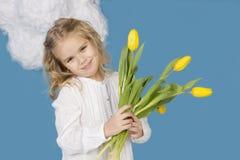 Mädchen, das einen Blumenstrauß von Tulpen lächelt und hält Stockfotos