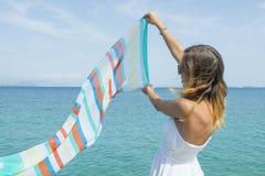 Mädchen, das einen bunten Schal auf Küste an einem sonnigen Sommertag wellenartig bewegt Stockfoto
