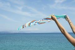 Mädchen, das einen colourfull Schal auf Küste wellenartig bewegt Lizenzfreies Stockfoto