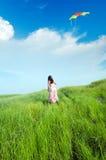 Mädchen, das einen Drachen auf dem Grasland fliegt Stockfotografie