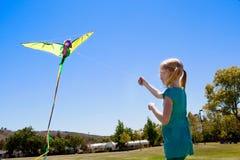 Mädchen, das einen Drachen fliegt Lizenzfreies Stockbild
