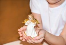 Mädchen, das einen Engel in ihrer Hand hält Stockbilder