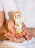 Mädchen, das einen Engel in ihrer Hand hält Lizenzfreie Stockfotos