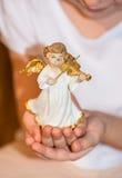 Mädchen, das einen Engel in ihrer Hand hält Stockfotografie