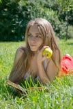 Mädchen, das einen gelben Apfel hält und ein Buch in einem Sommerpark liest Lizenzfreie Stockfotos