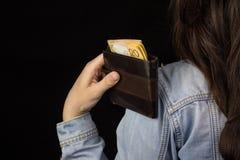 Mädchen, das einen Geldbeutel mit Geldeuro-Rückseitenansicht, Nahaufnahme, schwarzer Hintergrund, kaufend hält lizenzfreies stockfoto