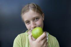 Mädchen, das einen grünen Apfel isst Stockfotografie