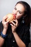 Mädchen, das einen großen Hamburger, Studiofoto isst Lizenzfreies Stockfoto