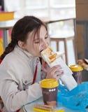 Mädchen, das einen Hotdog in einem Café isst Stockbild