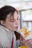 Mädchen, das einen Hotdog in einem Café isst Lizenzfreie Stockfotografie