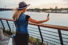 Mädchen, das einen Hut beim Nehmen von selfie durch den Fluss hält stockfotografie