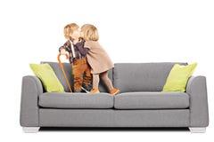 Mädchen, das einen Jungen bei der Stellung auf einem Sofa küsst stockfotos