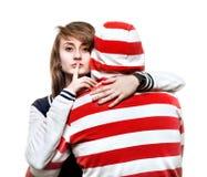 Mädchen, das einen jungen Mann in der Haube umarmt Lizenzfreie Stockbilder