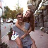 Mädchen, das einen Kerl in der Straße von einer Großstadt schön reitet Lizenzfreies Stockfoto