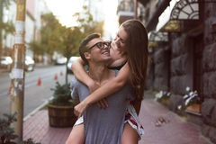 Mädchen, das einen Kerl in der Straße von einer Großstadt schön reitet Sie betrachten einander Stockfotografie