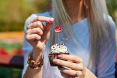 Mädchen, das einen kleinen Kuchen für hält Stockfotografie