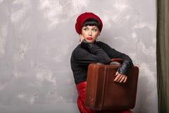Mädchen, das einen Koffer hält Lizenzfreie Stockfotos