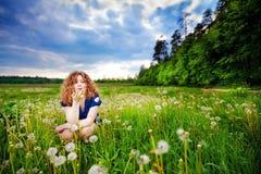 Mädchen, das einen Löwenzahn durchbrennt Lizenzfreie Stockfotografie