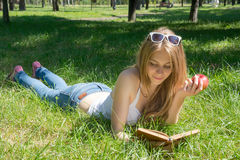 Mädchen, das einen roten Apfel hält und ein Buch in einem Sommer liest Lizenzfreie Stockfotografie