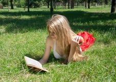 Mädchen, das einen roten Apfel hält und ein Buch in einem Sommer liest Lizenzfreies Stockfoto
