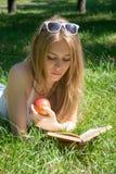 Mädchen, das einen roten Apfel hält und ein Buch in einem Sommerpark liest Lizenzfreie Stockfotos