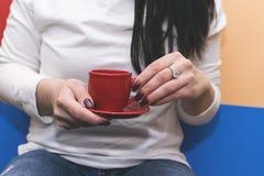 Mädchen, das einen roten Becher Kaffee hält Helle Fotos lizenzfreie stockfotos