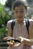 Mädchen, das einen Schmetterling hält Lizenzfreie Stockfotos
