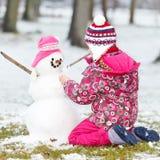Mädchen, das einen Schneemann aufbaut Lizenzfreie Stockfotografie