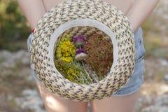 Mädchen, das einen Strohhut mit einem Blumenstrauß von schönen Blumen hält stockfoto