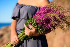 Mädchen, das einen Weidekrautblumenstrauß hält Stockfotografie