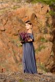 Mädchen, das einen Weidekrautblumenstrauß hält Stockfoto