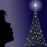 Mädchen, das einen Weihnachtsbaum schaut Lizenzfreies Stockbild