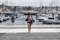 Mädchen, das einen Zebrastreifen und hinter einem Hafen kreuzt Stockfotografie