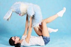 Mädchen, das in einer Haltung hält ein Spielzeugkaninchen in ihren Armen liegt Stockfoto