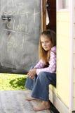 Mädchen, das in einer Tür sitzt lizenzfreie stockfotos