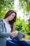 Mädchen, das an einer Tablette am grünen Parksommer arbeitet lizenzfreie stockfotografie